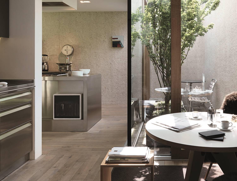 El cerramiento de cristal en forma de L de esta zona de la cocina permite que la luz natural del patio interior se cuele hasta la mesa del office.