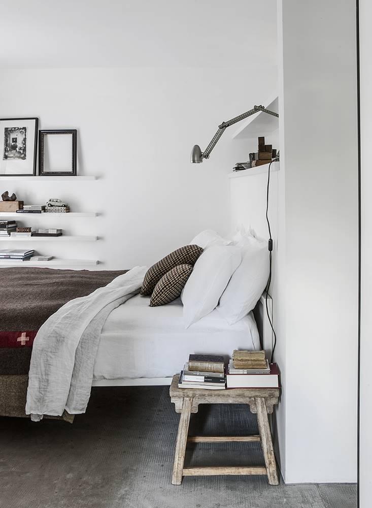 Un viejo taburete encuentra un nuevo uso como mesilla en este dormitorio.