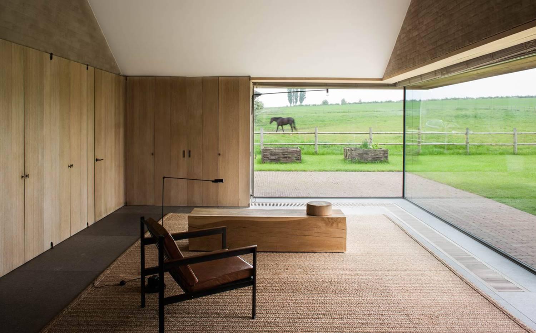 Alfombra de tejido natural, banco de madera y sillón de cuero en esta casa de Vincent Van Duysen.