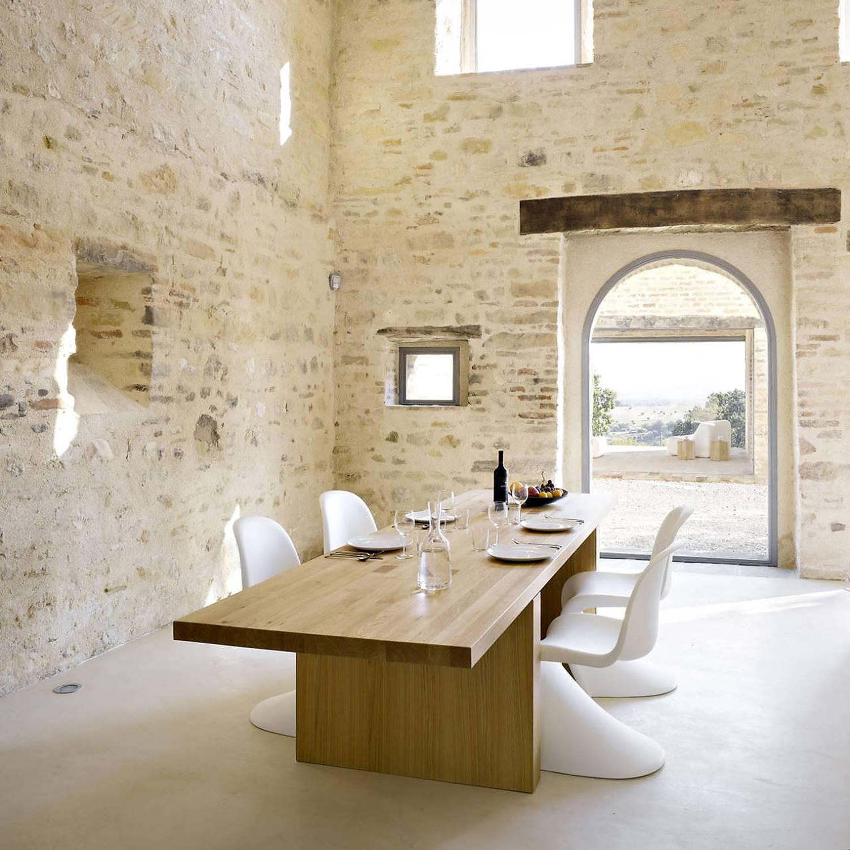 Muros de mampostería y mobiliario contemporáneo en la Casa Olivi, en Treia, Italia.