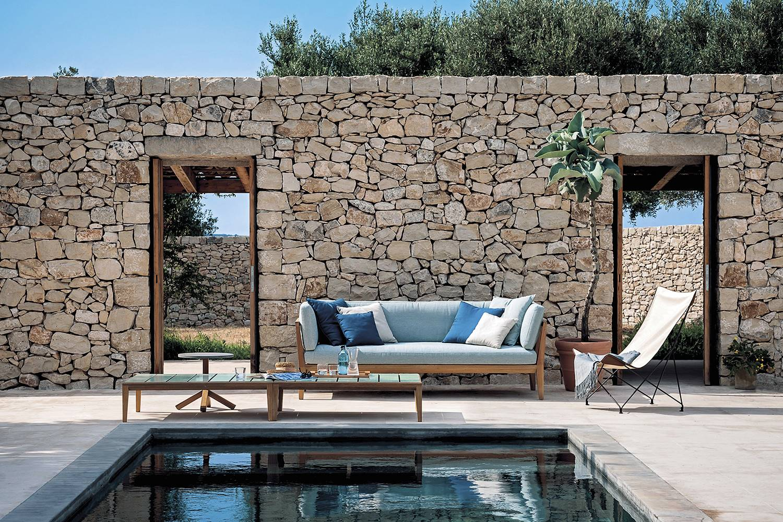 Mobiliario de exterior de la firma Roda frente a un muro rehabilitado.