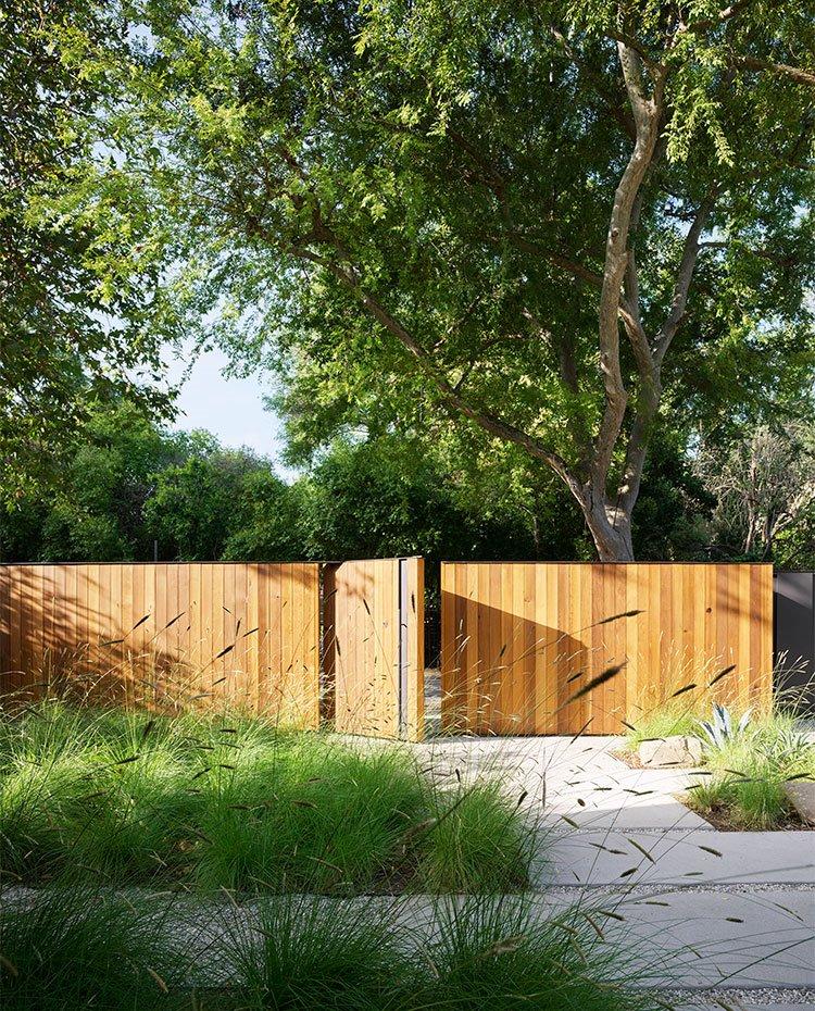 Acceso de entrada a vivienda con valla de listones de madera