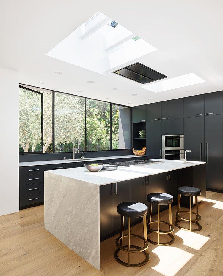 Cocina con amplia isla central de trabajo con encimera de mármol y mobiliario en negro, y lucernarios en el techo