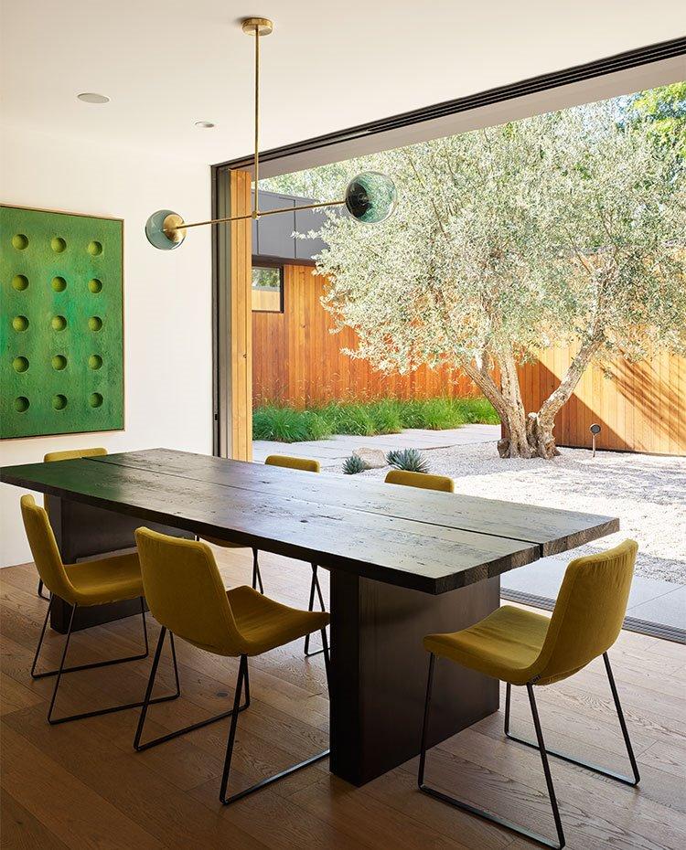 Comedor con mesa de centro de madera, sillas en color pistacho, luminaria suspendida, con gran apertura hacia exterior, suelo de madera