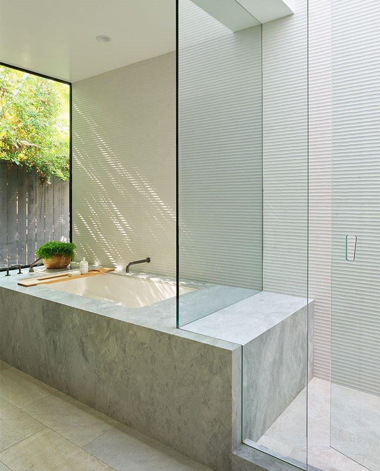 Cuarto de baño con ducha y bañera de obra de piedra con cerramientos acristalados