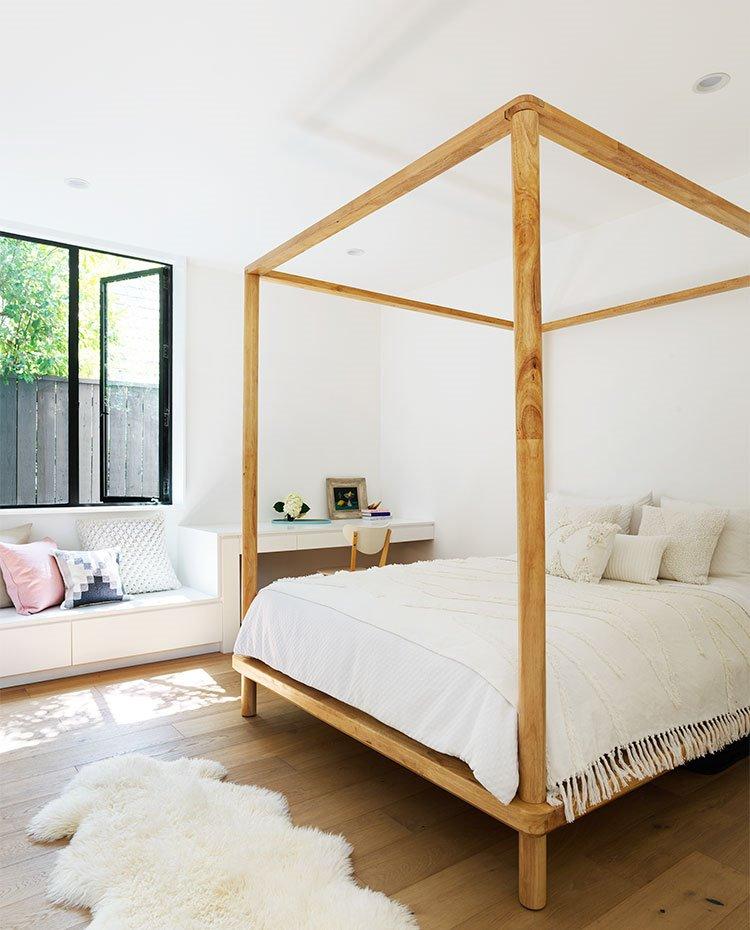 Cuarto de baño con estructura de cama en madera, mobiliario en blanco y rincon de trabajo