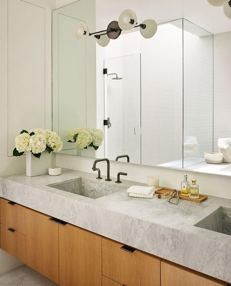 Cuarto-de-baño-con-mueble-suspendido-de-madera-y-amplio-espejo-frontal-en-zona-tocador