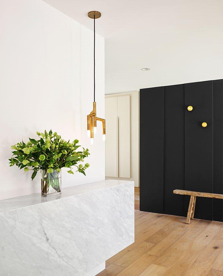 Detalle vestíbulo de entrada con mueble de mármol junto a jarrón con flores y luminaria suspendida en acabado dorado