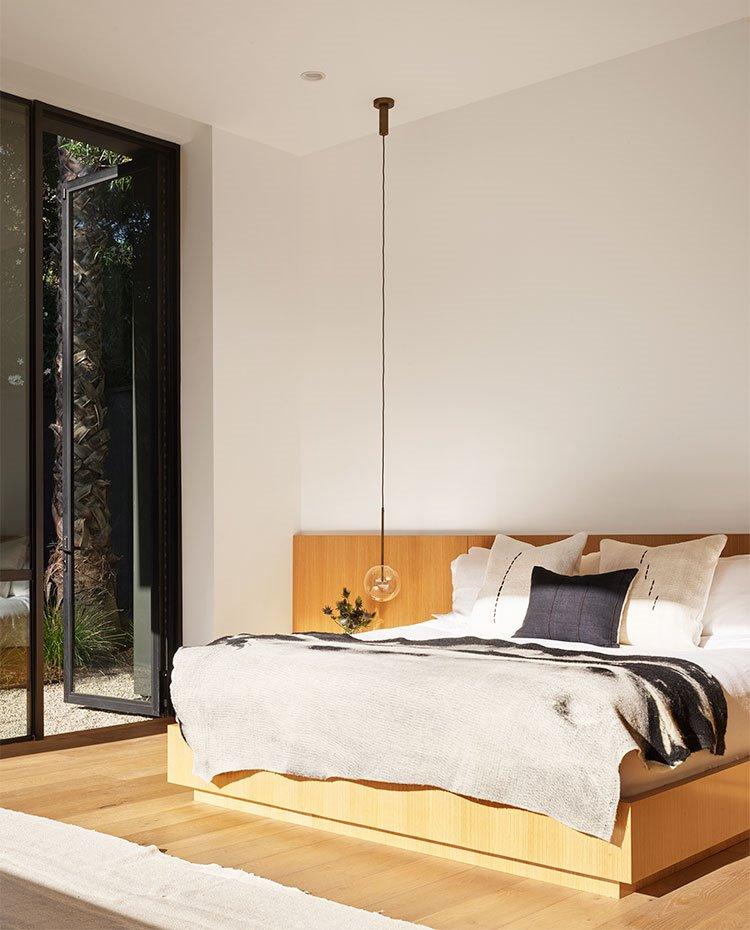 Dormitorio-principal-con-canapé-de-madera-y-apertura-acristalada-hacia-exterior
