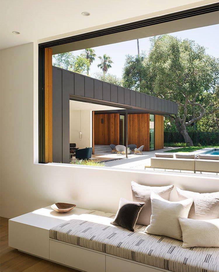 Mueble bancada con espacio para almacenaje, amplia ventana con cerramientos correderos hacia exterior de terraza