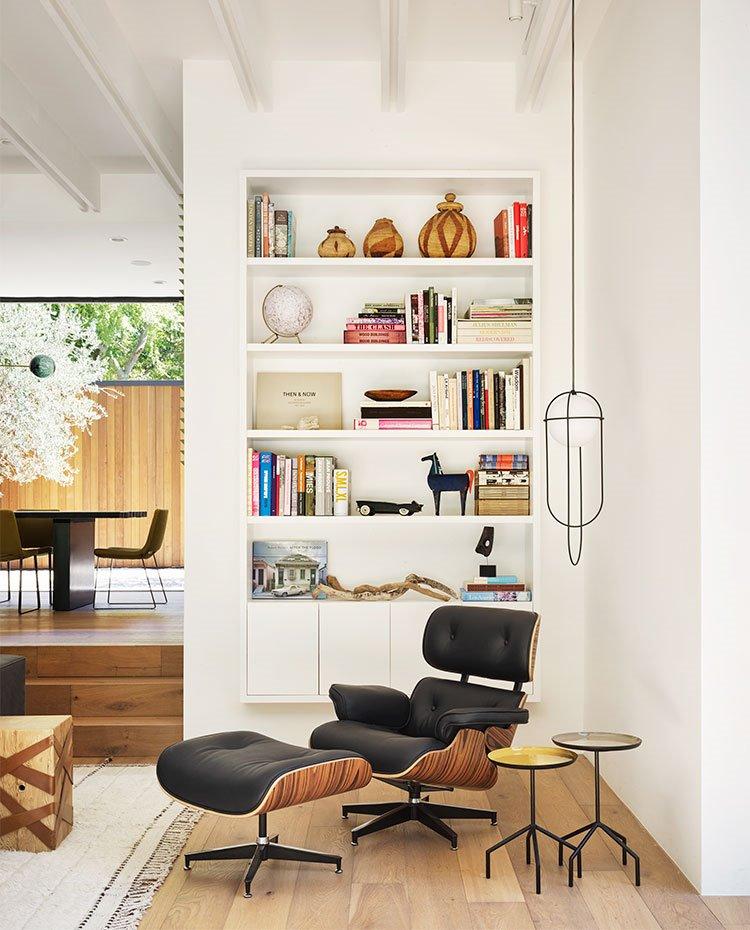 Rincón de lectura en salón con butaca y pouf en madera y piel, luminaria suspendida y librería en blanco suspendida en pared