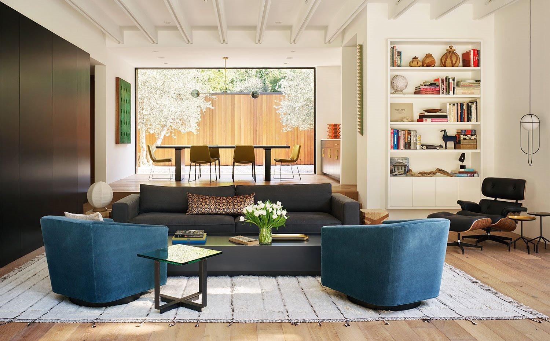 Salón con butacas tapizadas en azul oscuro, sofá y mesa en tonos oscuros sobre alfombra de tonos curdos