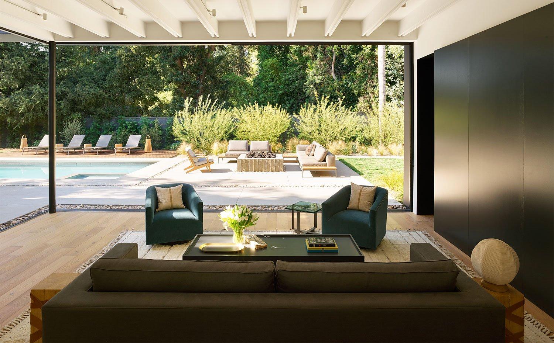 Salón con sofá y butacas en tonos oscuros, suelo de madera y acceso abierto hacia terraza y piscina