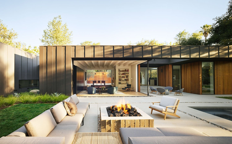 Terraza exterior con chimenea de obra, zona ajardinadaentorno a piscina y mobiliario exterior
