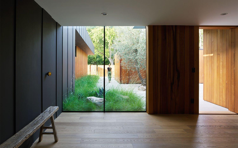 Vestíbulo de entrada con grandes aperturas, banco hecho de viga de madera, revestimientos con listones de madera