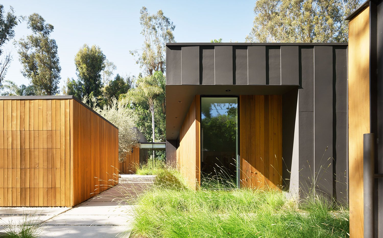 Vista exterior de estructura de vivienda en madera y hormigón y con amplias aperturas en fachada, zona de paso en bloques de hormigón