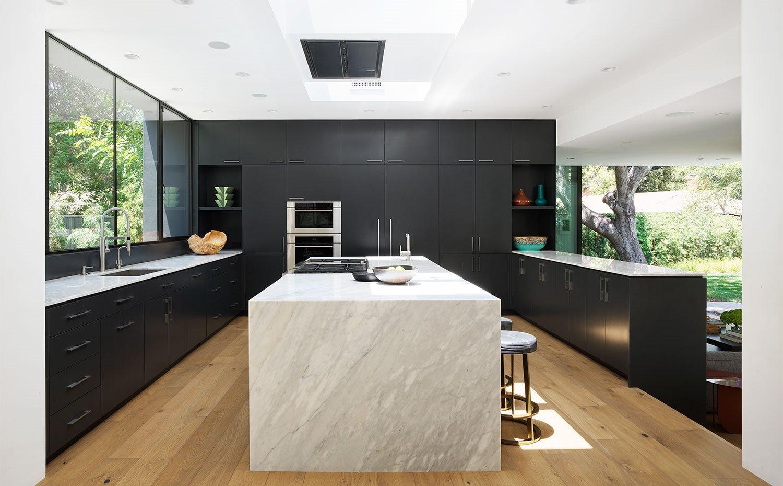 Vista frontal de la cocina abierta con zona de cocción isla con taburetes para zona de office.