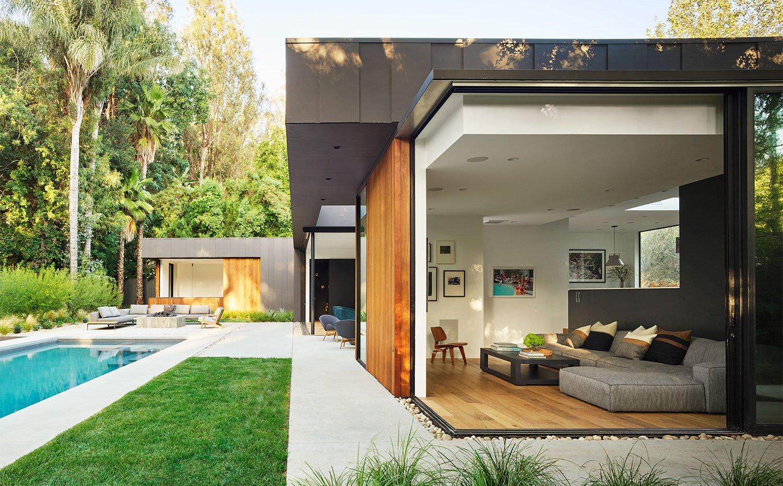 Vista lateral con terraza con piscina e interior de casa con salón abierto al exterior