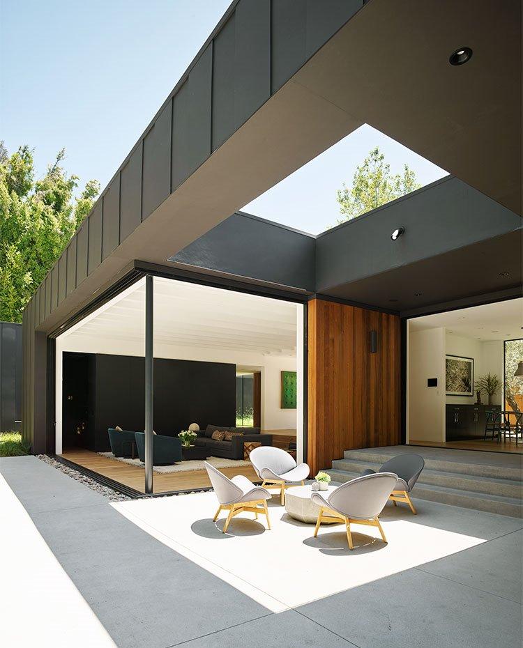 Zona de estar exterior con amplio lucernario en la estrucutra, junto a salón interior, pavimento de hormigón y mobiliario en color gris