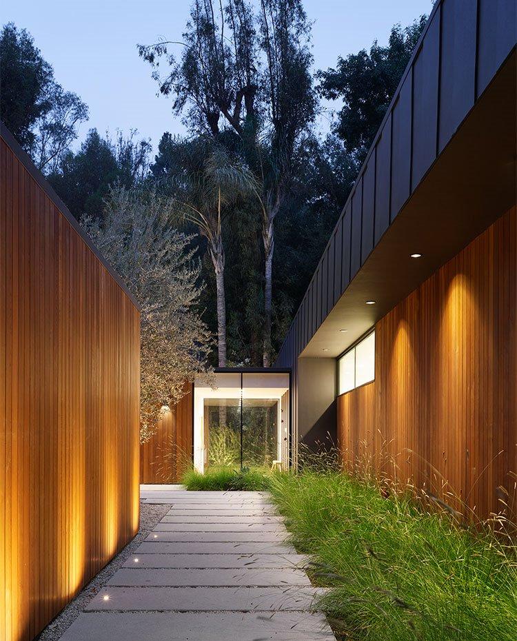 Zona de paso exterior con estructuras revestidas de madera, luminarias exteriores indirectas y puntuales integradas en el camino de hormigón