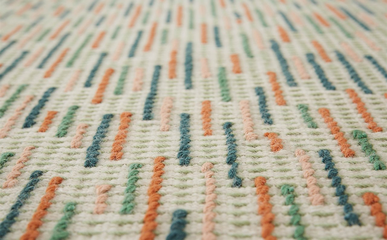 Detalle de la alfombra Backstitch Busy Green, de Raw-Edges para GAN.