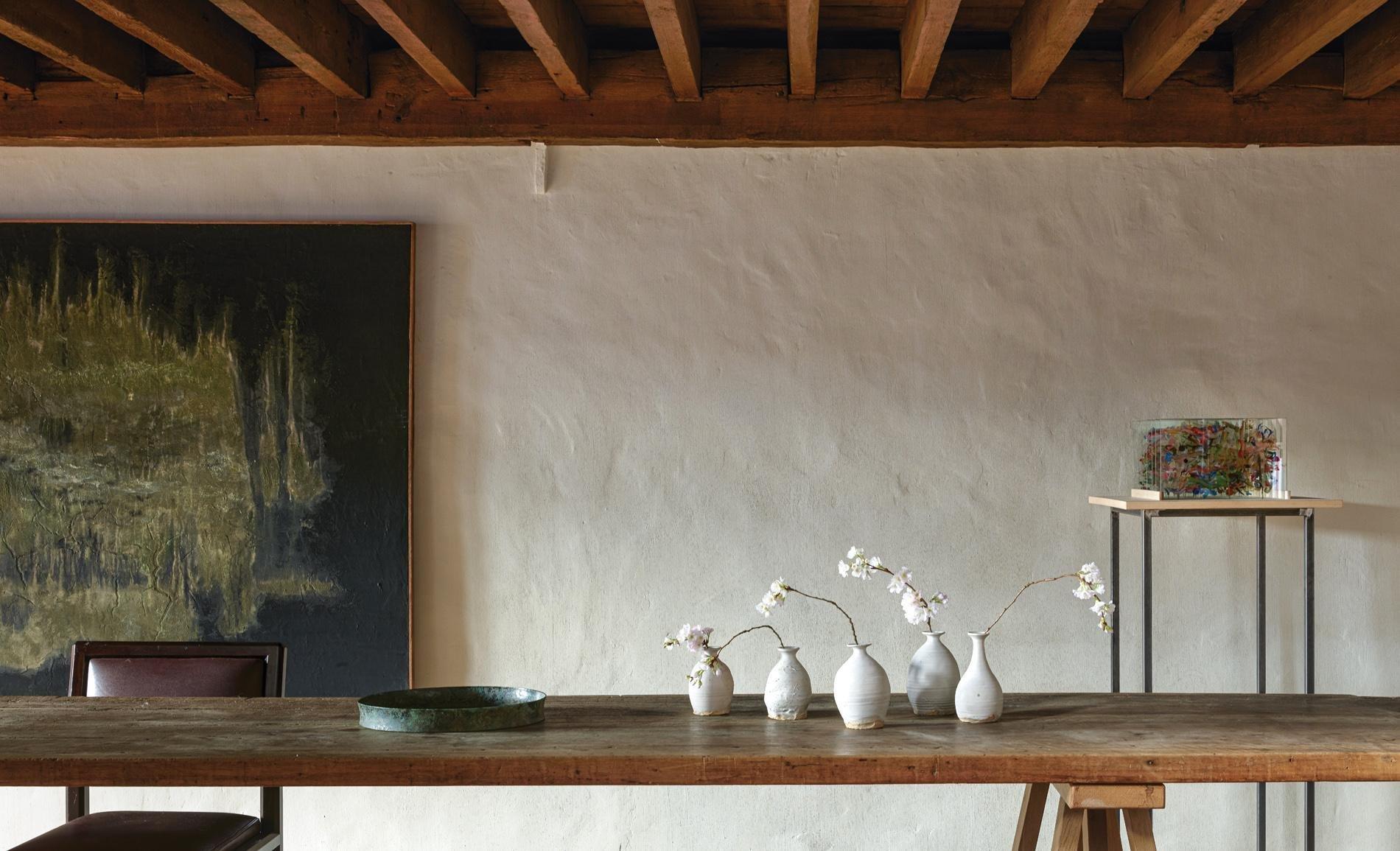 Espacio del diseñador Axel Vervoord con a¡paredes blancas y rugosas y vigas de madera