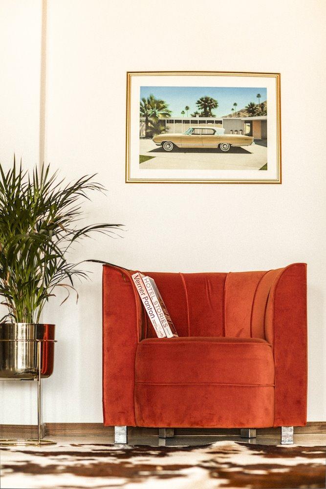 Sillón de terciopelo rojo con cuadro de un coche clásico de Danny Hellard.